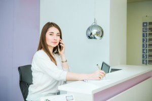 Portrait of friendly young woman looking at camera, talking on phone behind the reception desk. Administrator in the office, clinic, center, hotel. Occupation concept. Selective focus, space for text