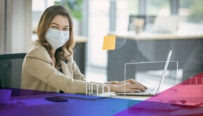 Masked woman working on her computer